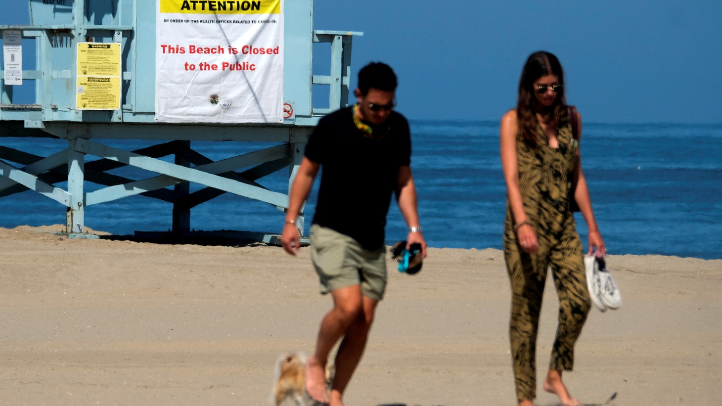 """People walk past a """"beach closed"""" sign during the outbreak of the coronavirus disease (COVID-19) at Venice Beach in Los Angeles, California, U.S., July 4, 2020."""