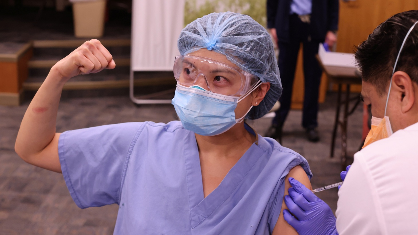 Physician Joyce Limurti, 40, flexes her bicep as she is given the coronavirus disease (COVID-19) vaccine at Dignity Health Glendale Memorial Hospital and Health Center in Glendale, California, U.S., December 17, 2020.