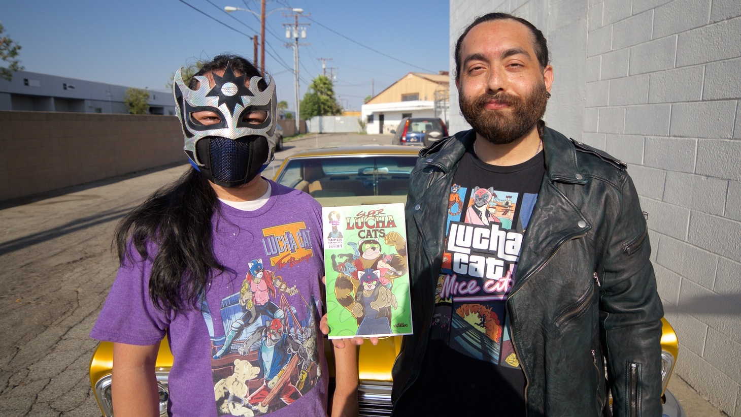 """Javier Solórzano (right) holds up the first issue of """"Super Lucha Cats."""""""
