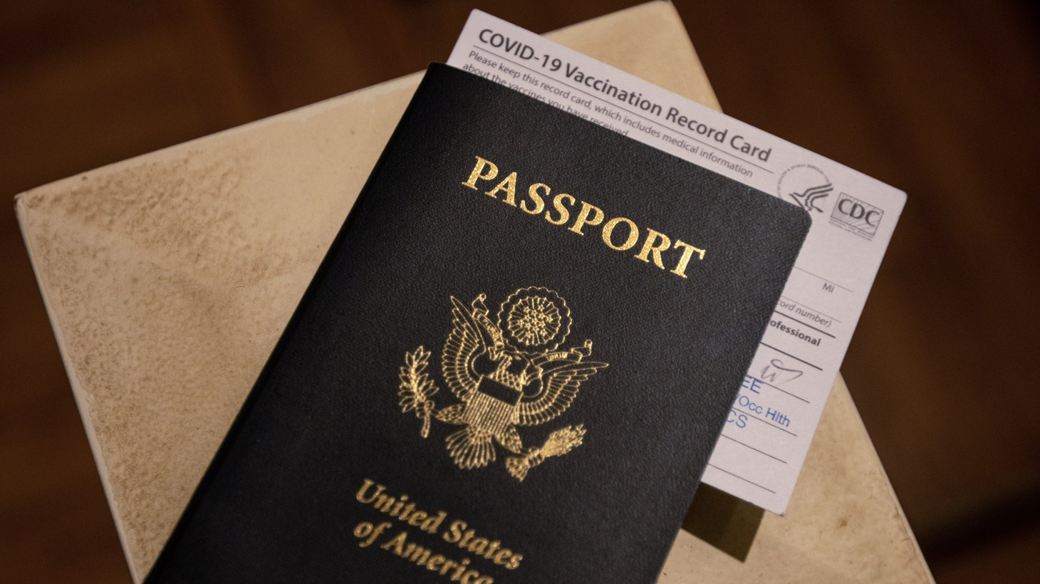An illustration of a United States Passport with a COVID-19 Vaccination Record Card in a home in San Diego, California, March 11, 2021. Some European countries such as Spain, Georgia, Greece, and Denmark will allow international travelers who have received the COVID-19 vaccine.