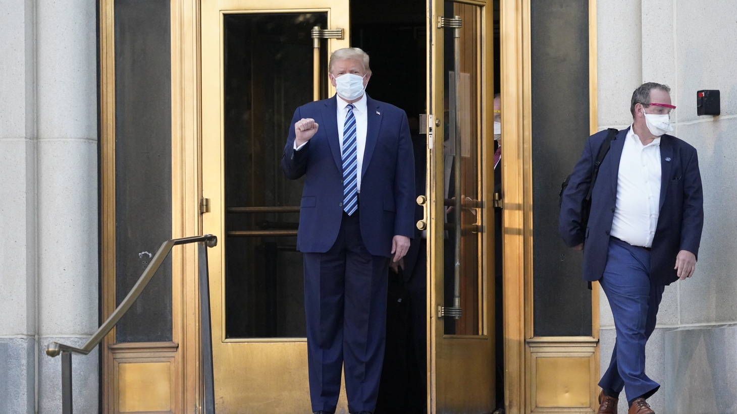 Donald J. Trump, wearing a mask, emerges from the front door of Walter Reed National Military Medical Center to board Marine One for a return trip to the White House after receiving treatment for a COVID-19 infection. October 5, 2020, Bethesda, Maryland.