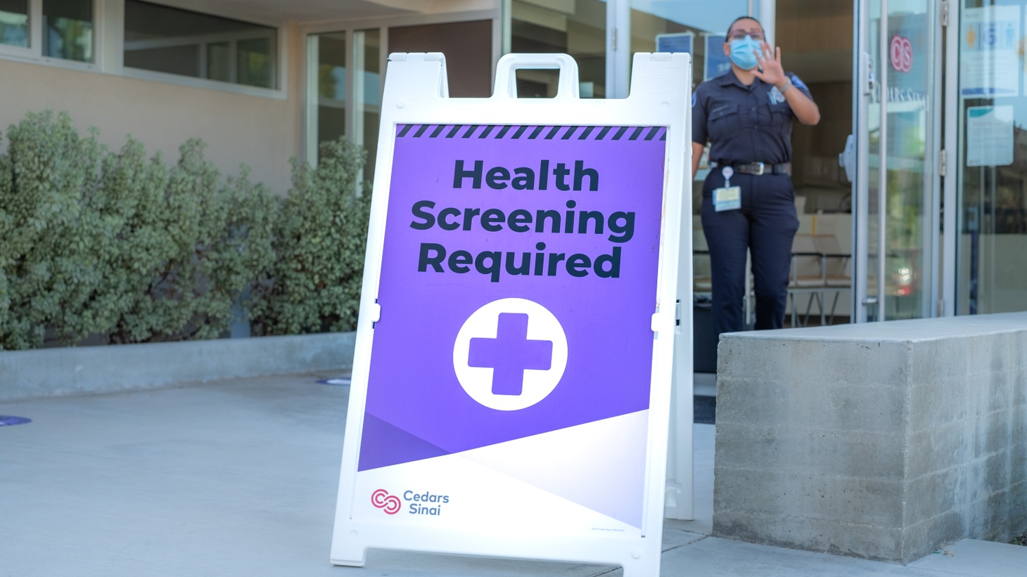 A health screening sign sits outside Cedars Sinai Urgent Care in Culver City.