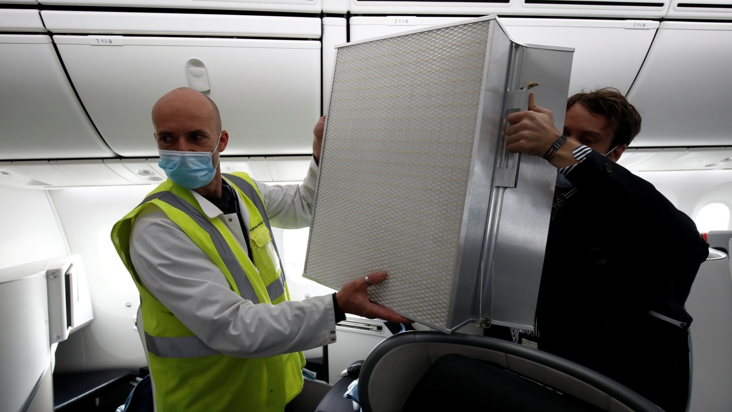 An employee wearing a protective face mask displays a Donaldson air filter in an Air France Boeing 787 aircraft during a presentation of new security and health measures at Paris Charles de Gaulle airport in Roissy-en-France during the outbreak of the coronavirus disease (COVID-19) in France, May 6, 2020.