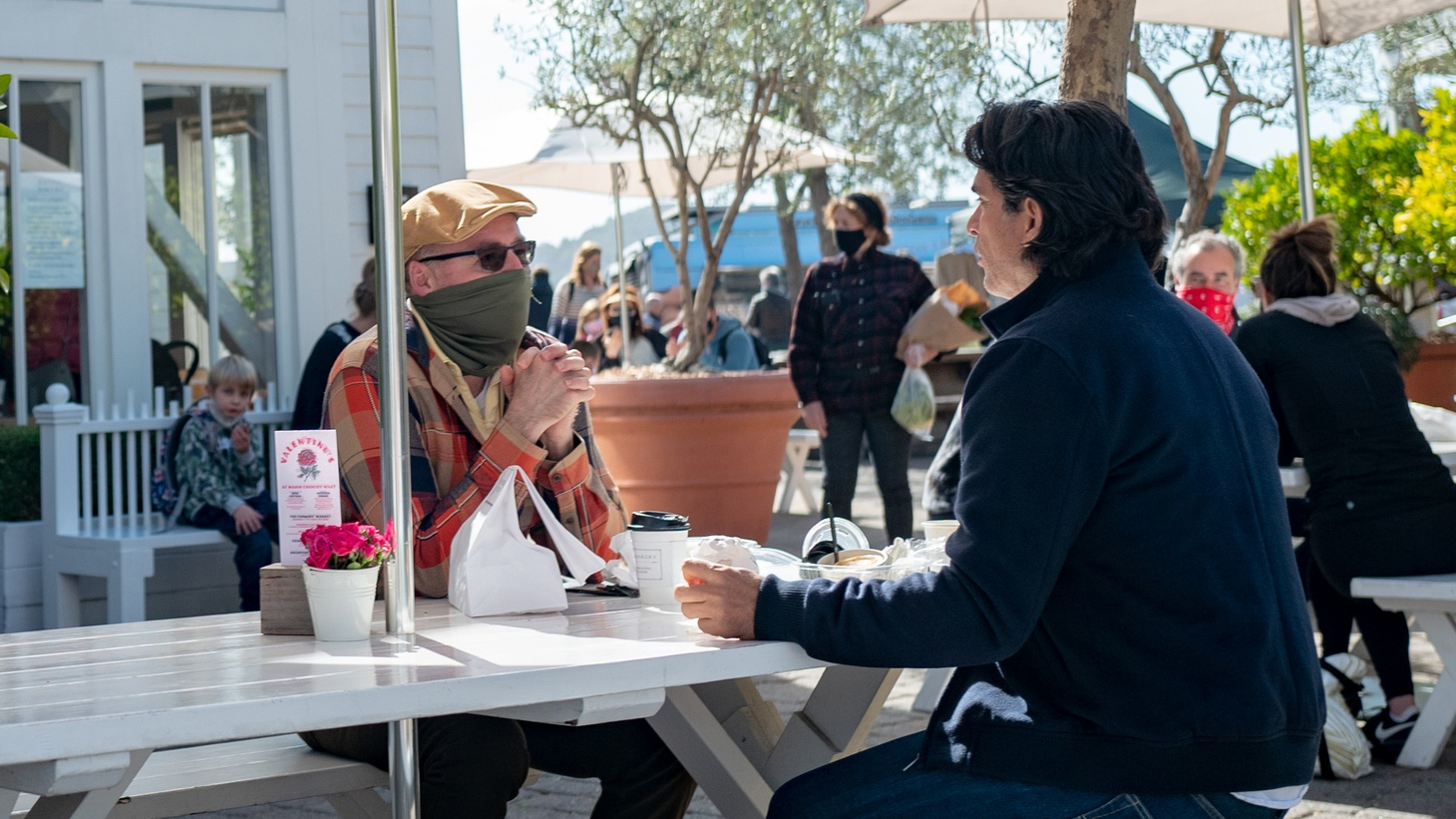 Two men, including one wearing a bandana face mask, sit at a restaurant patio table in Larkspur, California, February 13, 2021.