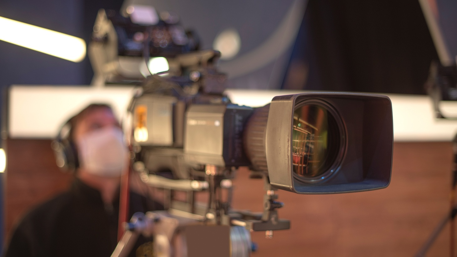 A masked cameraman films a television show in a studio.