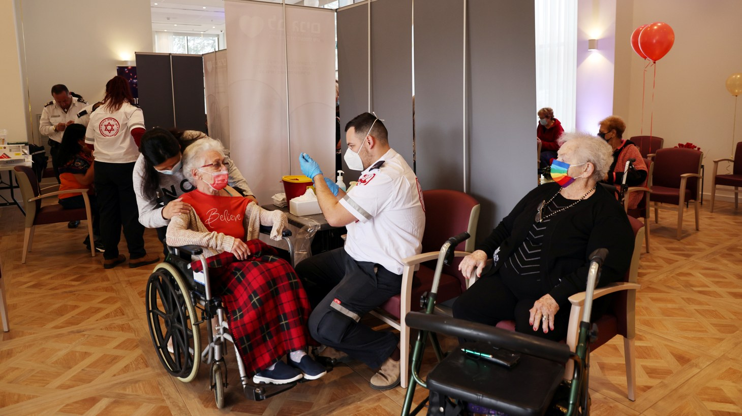 Residents of an assisted living facility receive their vaccination booster shots against the coronavirus disease (COVID-19) during a party celebrating the residents receiving their second dose of the vaccine, in Netanya, Israel, January 19, 2021.
