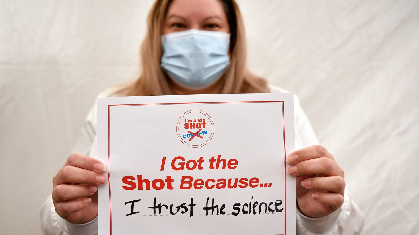 """Cathy Vasquez, a clinical research nurse at Inspira Medical Center Vineland, holds a sign that says """"I got the shot because I trust the science,"""" after receiving a COVID-19 vaccination in Vineland, N.J., Friday, Dec. 18, 2020."""