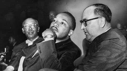 Martin Luther King and Governor Edmund G. Brown during a Freedom Rally at the Los Angeles Sports Arena. An audience of 12,000 was expected at the 18,000-seat venue. When over 25,000 people showed up to hear King speak, many remained outside and listened to the speech over loudspeakers. Photograph dated June 18, 1961.