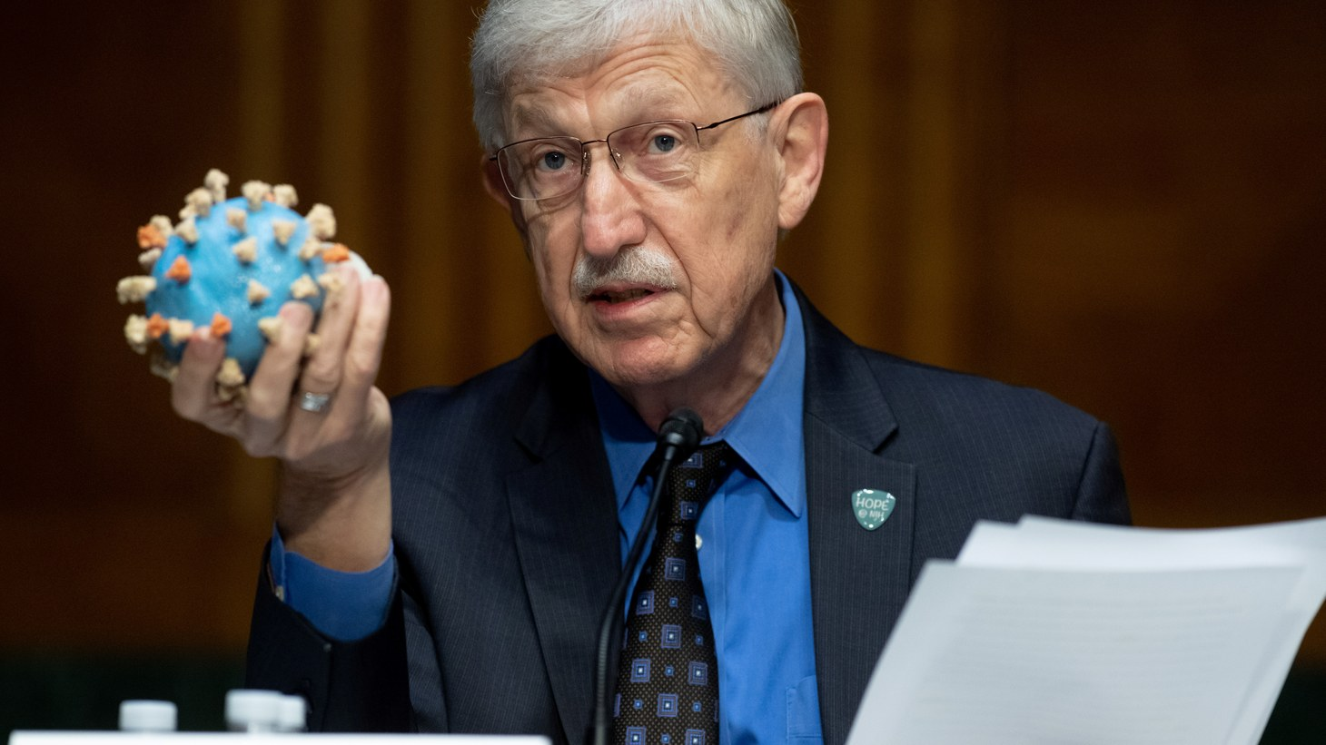 Dr. Francis Collins, Director of the National Institutes of Health (NIH), holds up a model of SARS-CoV-2, known as the novel coronavirus, during a U.S. Senate Appropriations Subcommittee Hearing on the plan to research, manufacture, and distribute a coronavirus vaccine. Washington, D.C, U.S., July 2, 2020.