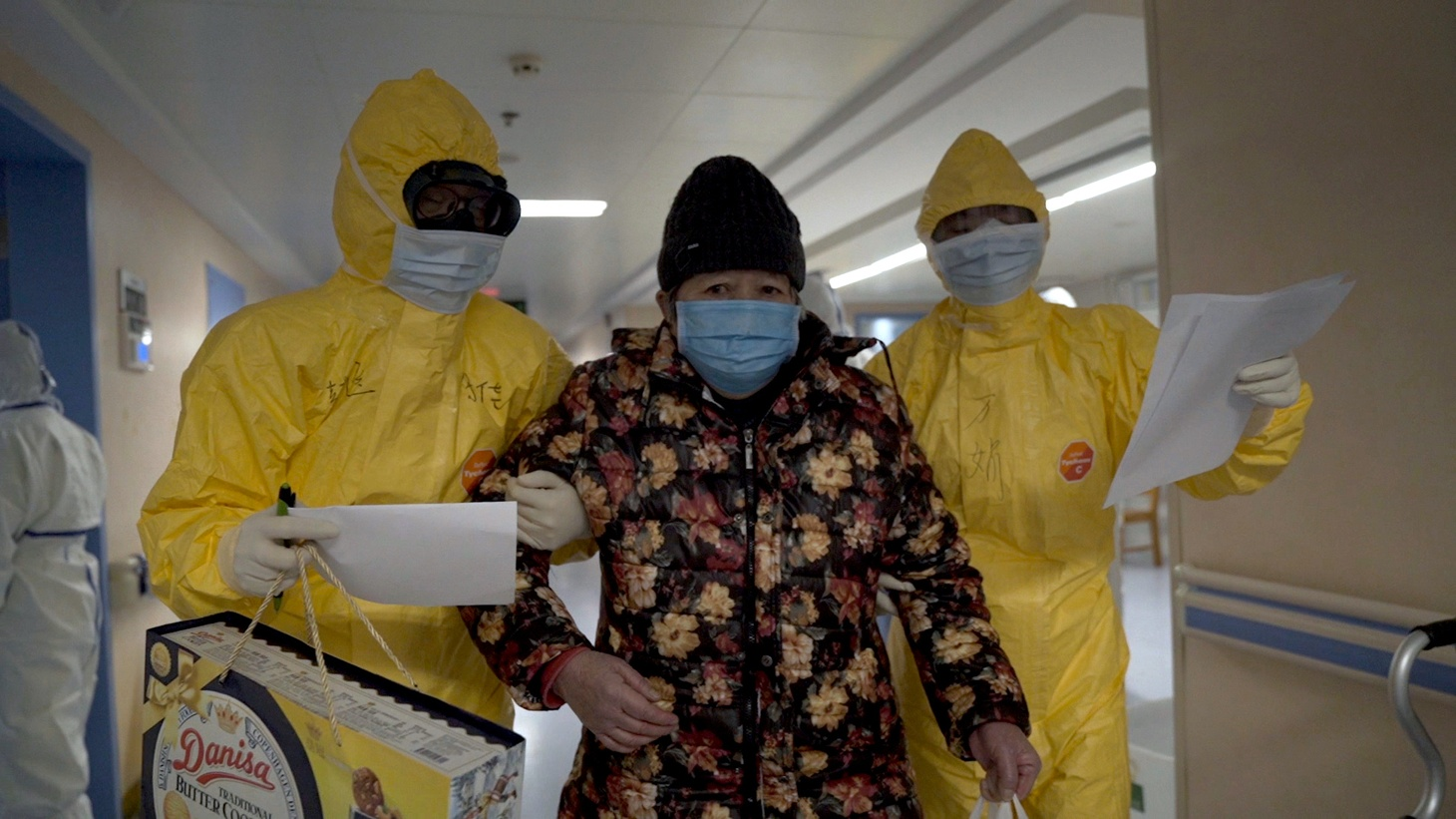 """Health workers with a woman inside a hospital in Wuhan, China in """"76 Days."""""""