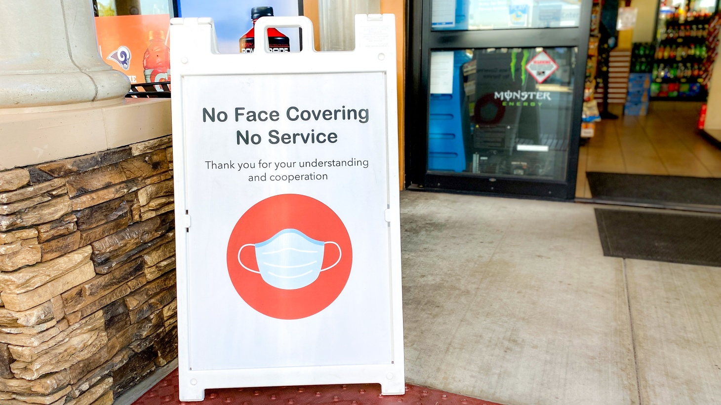 """A sign outside a gas station convenience store says, """"No face covering, no service. Thank you for your understanding and cooperation."""" Newport Beach, California, December 6, 2020."""