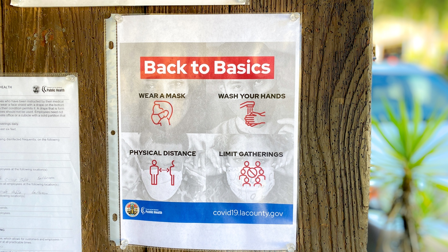 "An LA County Department of Public health sign is pinned at the entrance of a market in Topanga Canyon. It says, ""Back to basics. Wear a mask. Wash your hands. Physical distance. Limit gatherings."" December 5, 2020."