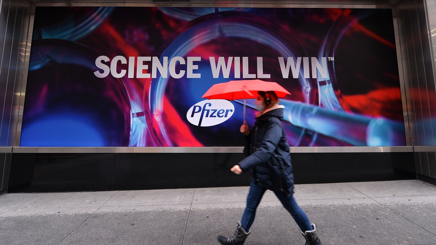 """A woman holding an umbrella walks past the Pfizer world headquarters in New York, NY, December 4, 2020. The artwork on the wall says """"Science will win."""" On December 11, 2020, the U.S. Food and Drug Administration authorized Pfizer's COVID-19 vaccine for emergency use."""