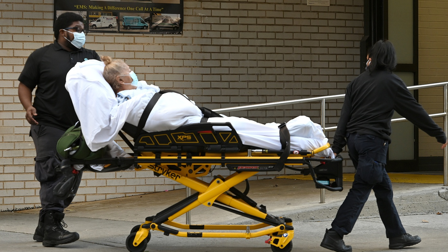 A woman lying on a stretcher is wheeled out of Long Island Jewish Forest Hills Northwell Health Hospital in the Queens borough of New York City, NY, November 10, 2020. The United States is experiencing a surge in COVID-19 cases as it recently surpassed 10 million in the number of people infected with coronavirus.