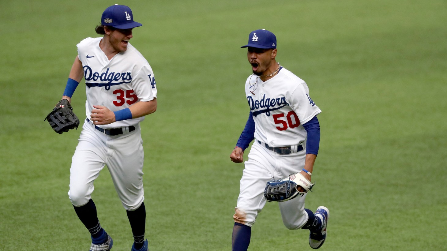 Los Angeles Dodgers right fielder Mookie Betts, right, celebrates with center fielder Cody Bellinger after Betts made a catch against the outfield wall, robbing a home run from the Atlanta Braves' Marcell Ozuna during the fifth inning in game six of the National League Championship Series on Saturday, Oct. 17, 2020, at Globe Life Field in Arlington, Texas. The Dodgers won, 3-1, to force a Game 7 on Sunday.