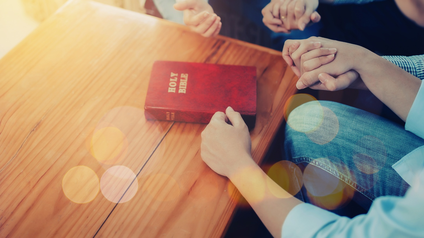 People hold hands as they sit indoors in front of a Bible. On April 9, 2021, the Supreme Court ruled that California cannot stop people from gathering in homes for religious purposes.