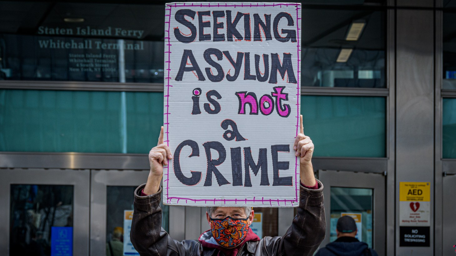 """A man holds a sign saying, """"Seeking asylum is not a crime"""" in Manhattan, New York, April 22, 2021."""