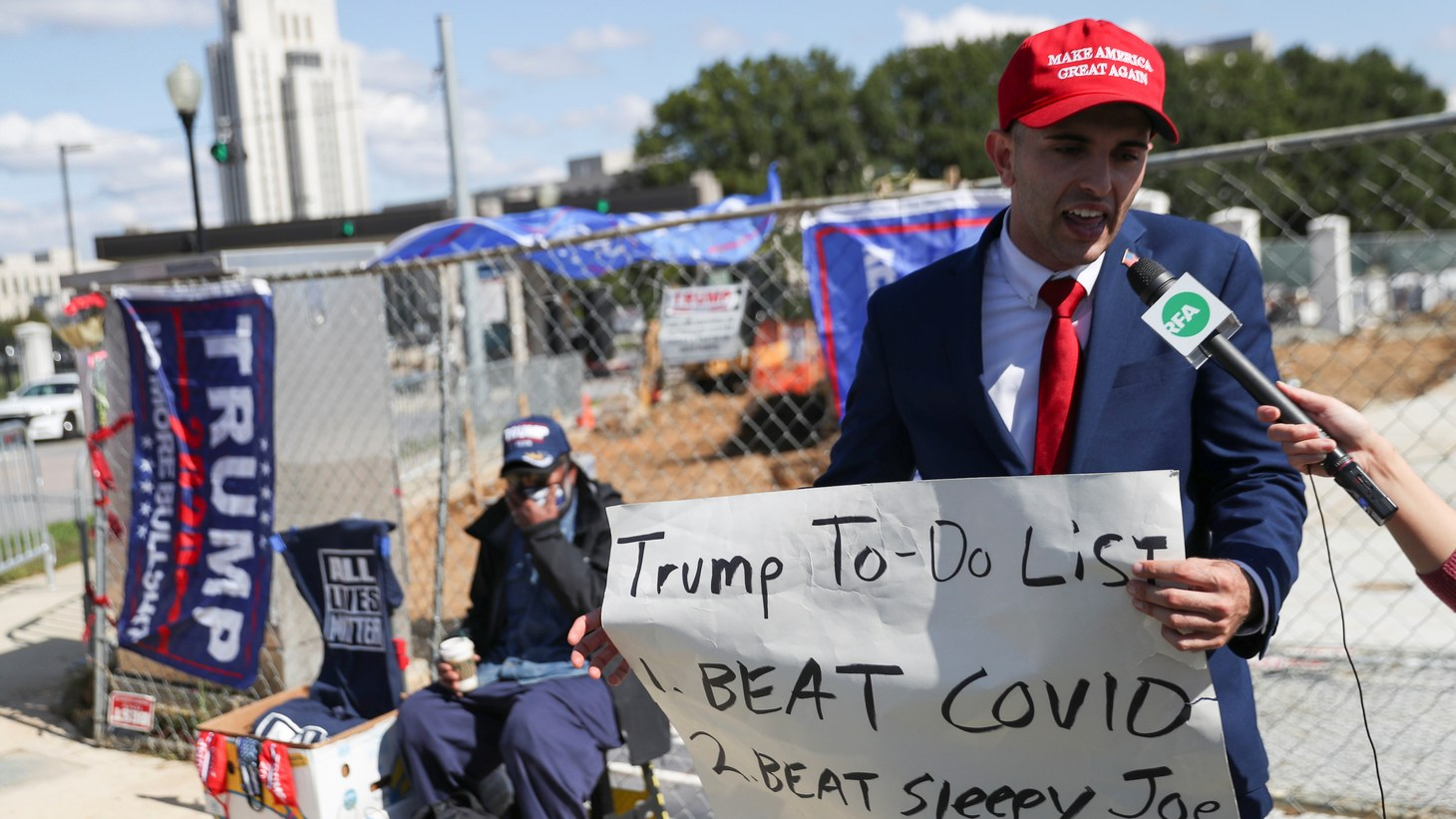 A supporter of U.S. President Donald Trump holds a sign as he talks to the media outside Walter Reed National Military Medical Center, where Trump is being treated for COVID-19 in Bethesda, Maryland, U.S. October 5, 2020.