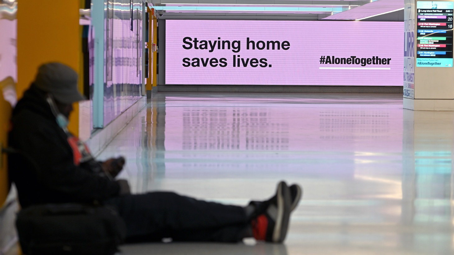 A man sits on the floor of Penn Station as an electronic billboard in the background reminds commuters that not traveling is the best way to keep coronavirus from spreading as Thanksgiving nears, New York, NY, November 17, 2020.