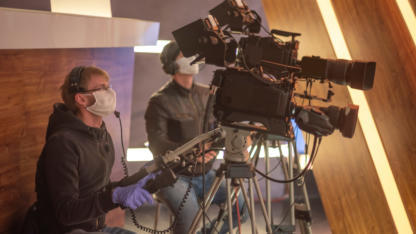 Masked cameramen are filming a television show in a studio.