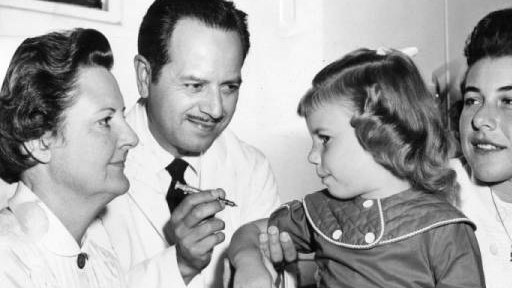 Patti Benton, 4, prepares to receive a polio immunizing shot. Dr. Mario De Lara administers the shot with assistance from Mrs. Earl Hazelett, left registered nurse, and Mrs. William Benton, member of Junior Woman's club. October 15, 1958.