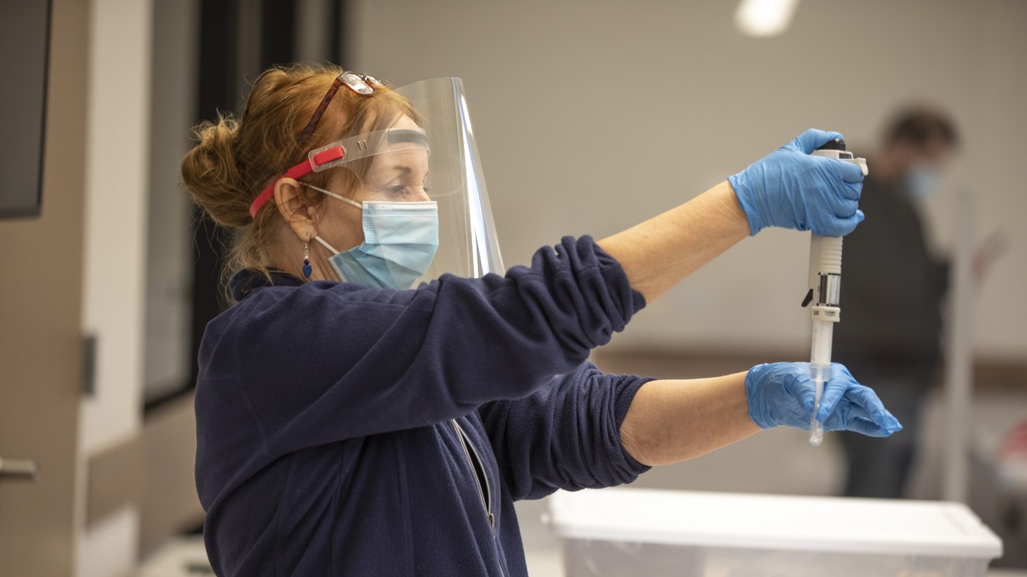 A worker holds a medical instrument inside Veterans Memorial Center in Davis, California, where UC Davis staff, students, and residents of the area received free COVID-19 tests, as part of the Healthy Davis Together project. January 28, 2021.