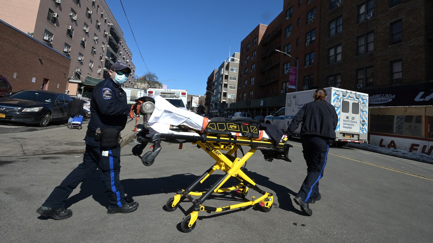 Two EMTs return to their ambulance with their stretcher after dropping off a patient at Elmhurst Hospital Center in the Queens borough of New York City, NY, February 21, 2021.