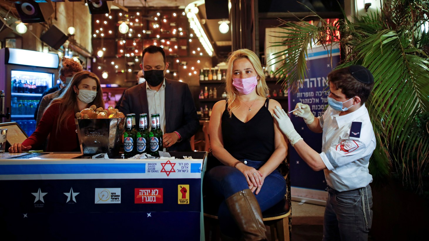 A woman receives a vaccination against the coronavirus disease (COVID-19) as part of a Tel Aviv municipality initiative offering a free drink at a bar to residents getting the shot, in Tel Aviv, Israel, February 18, 2021.