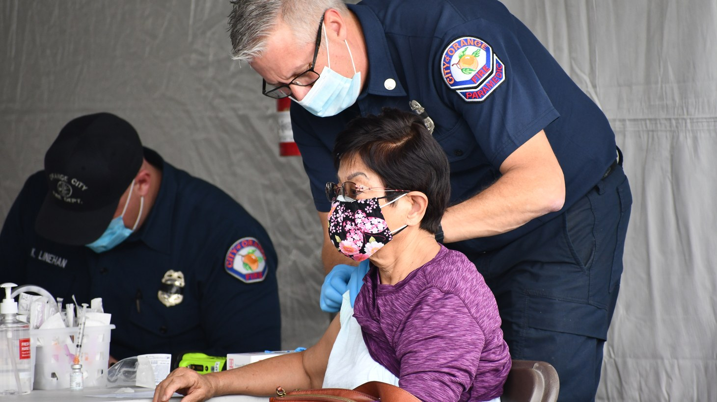 An Orange County paramedic administers the coronavirus vaccine to patients at the Disneyland Resort vaccination site, January 13, 2021.