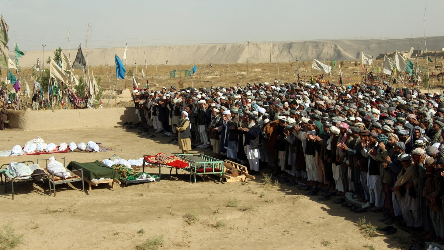 Afghans perform prayers at the funeral for the victims killed by an airstrike called in to protect Afghan and U.S. forces during a raid on suspected Taliban militants, in Kunduz, Afghanistan, November 4, 2016.