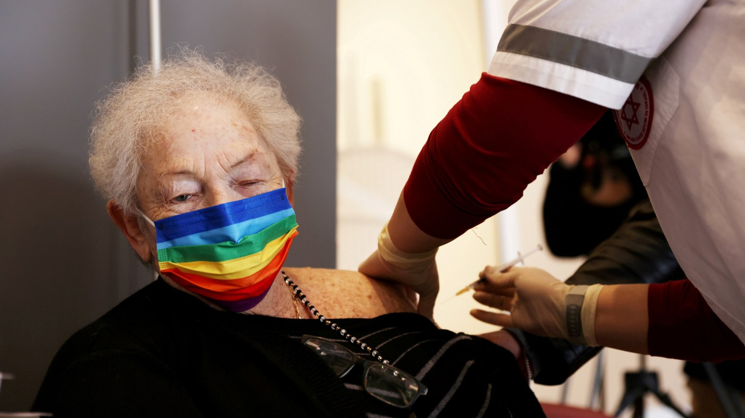 An elderly woman receives a booster shot of her vaccination against the coronavirus disease (COVID-19) at an assisted living facility, in Netanya, Israel January 19, 2021.