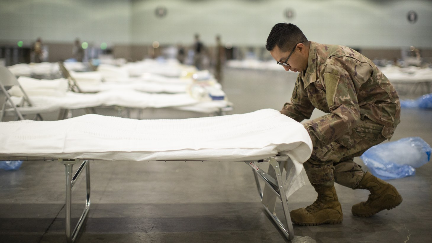 A member of the California National Guard puts sheets on a hospital bed while setting up a Federal Medical Station inside the Los Angeles Convention Center, March 29, 2020.