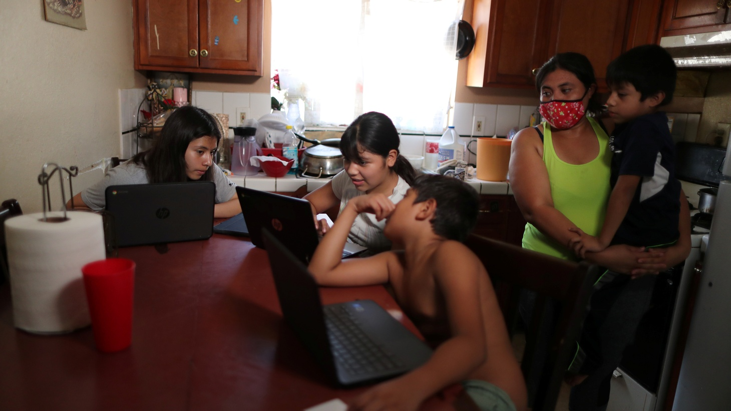 Los Angeles Unified School District students Keiley Flores, 13, Andrea Ramos, 10, Alexander Ramos, 8, work on school-issued computers with unreliable internet connectivity at their Los Angeles home during the COVID-19 pandemic. Their mother Anely Solis, 32, and their brother Enrique Ramos, 5, look on. August 18, 2020.