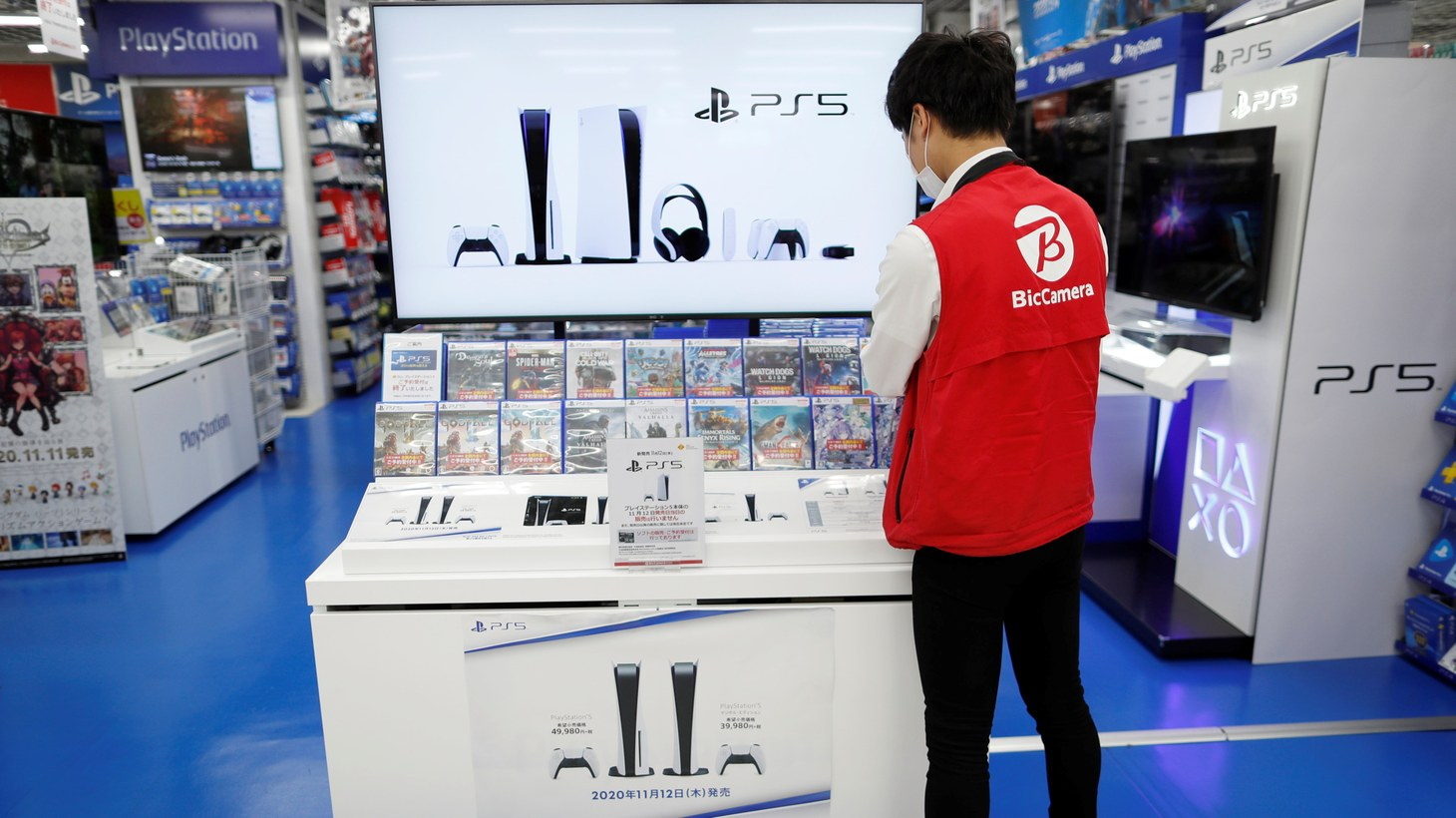An employee of the consumer electronics retailer chain Bic Camera works at the promotion display for the Sony PlayStation 5 game console and its gaming softwares in Tokyo, Japan, November 10, 2020.