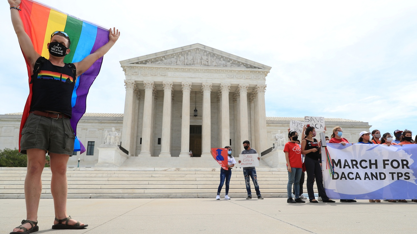 Joseph Fons holds a Pride flag beside DACA activists outside of the U.S. Supreme Court in Washington, U.S., June 15, 2020.
