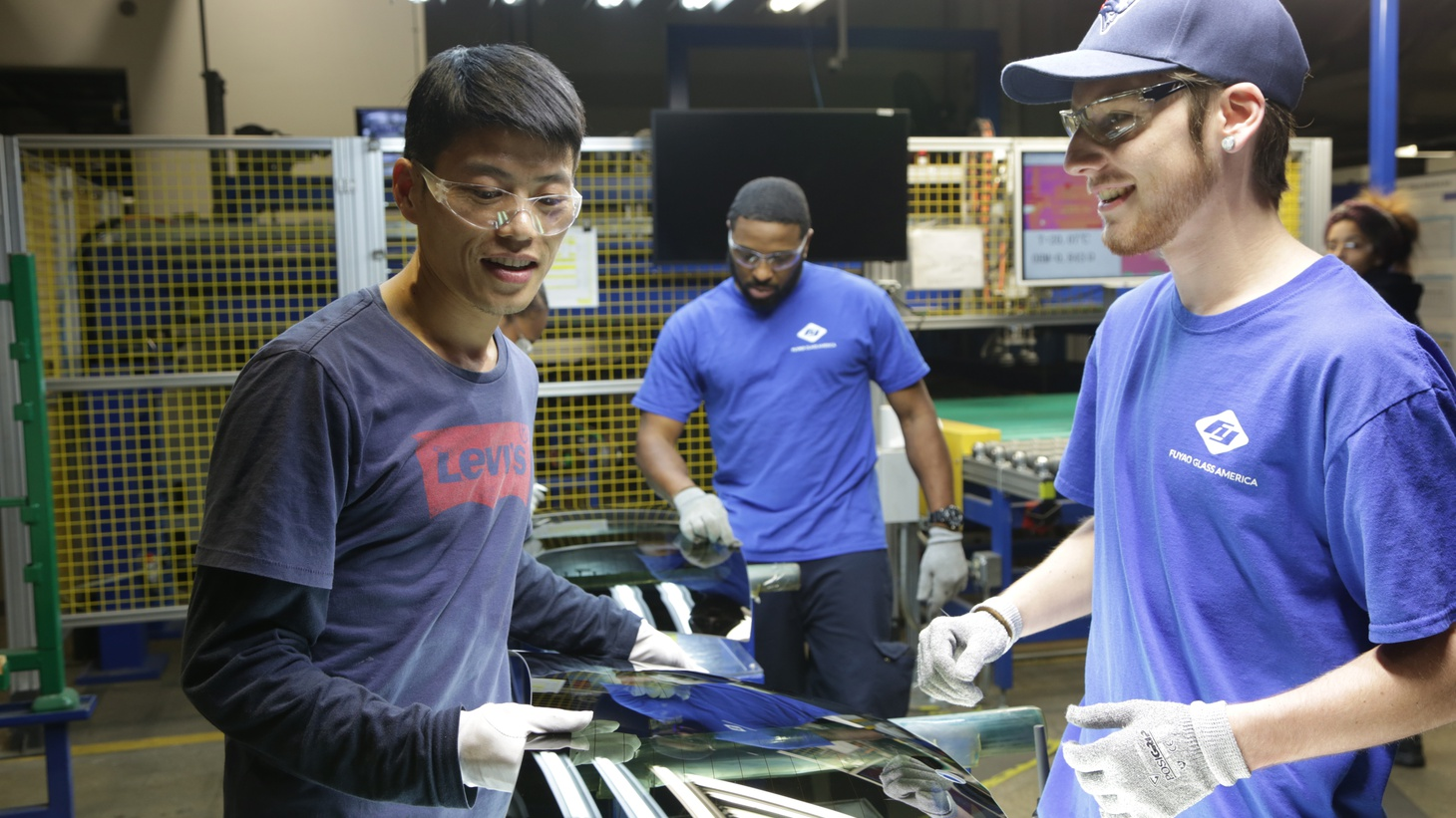 "Wong He (left) working with Kenny Taylor (center) and Jarred Gibson (right) in the furnace tempering area of the Fuyao factory in Dayton, Ohio from the film ""American Factory."""