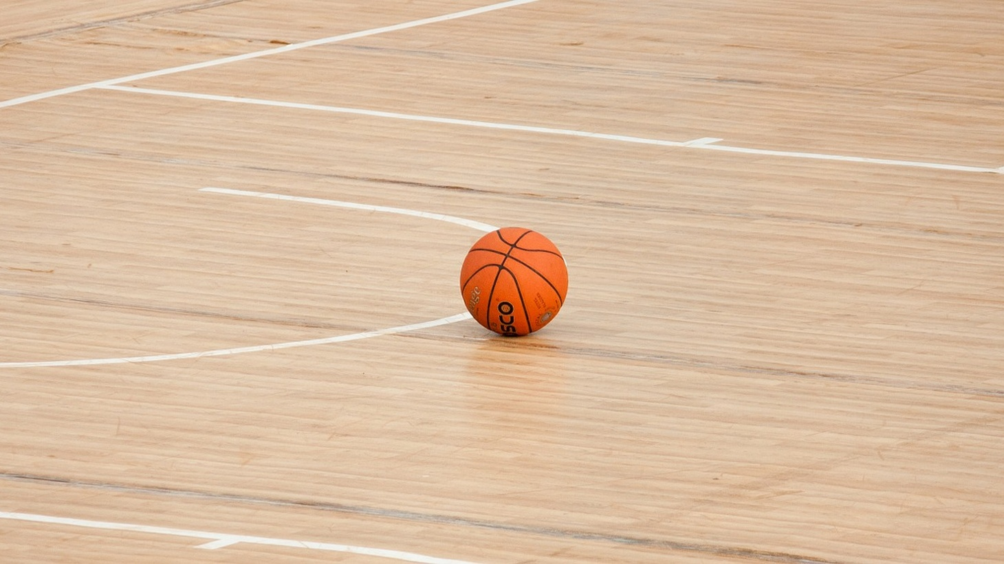 A lone basketball on the court.