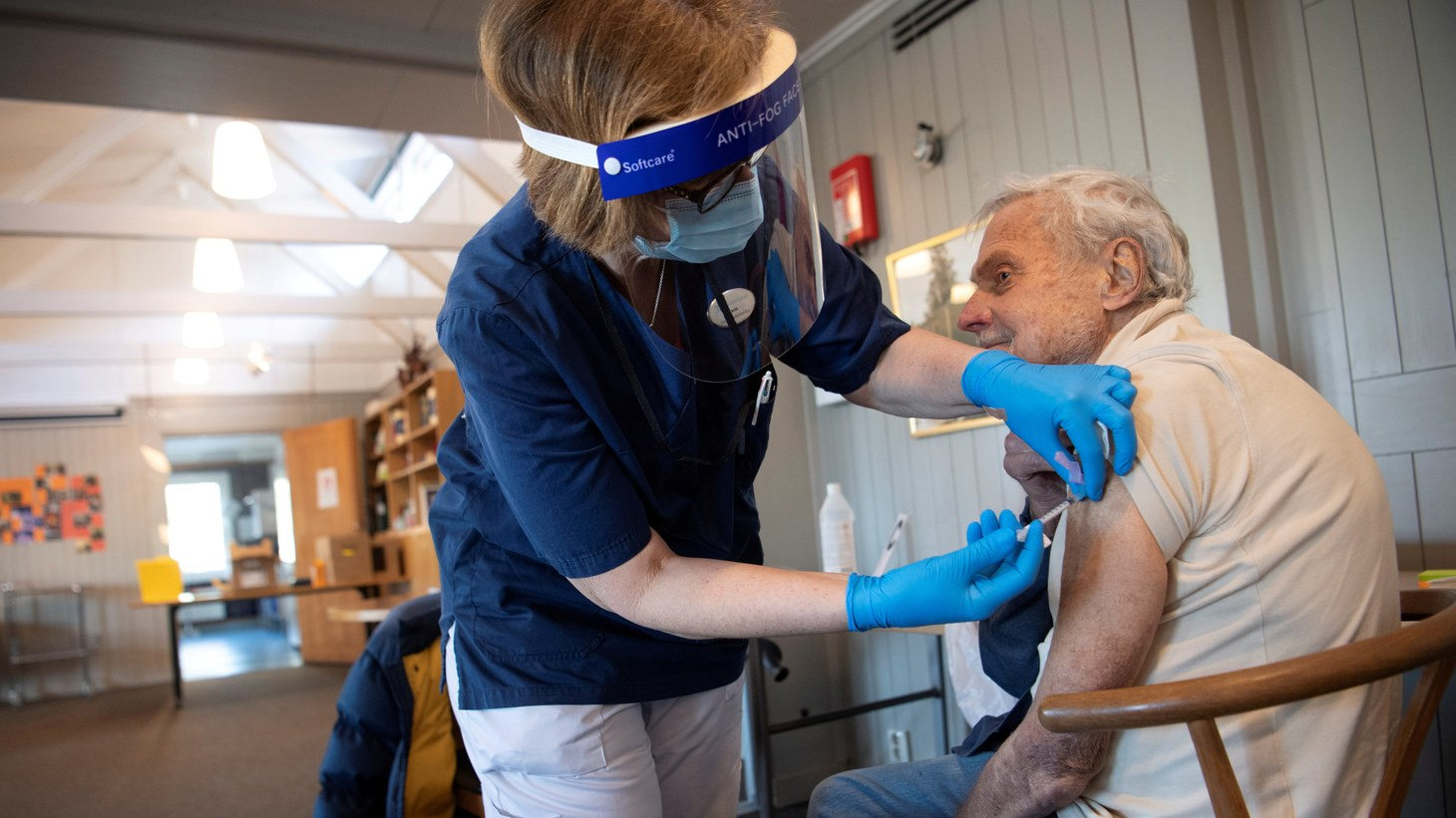 A health worker vaccinates an elderly person with Pfizer's COVID-19 vaccine at a temporary vaccination clinic in a church in Sollentuna, north of Stockholm, Sweden, March 2, 2021.