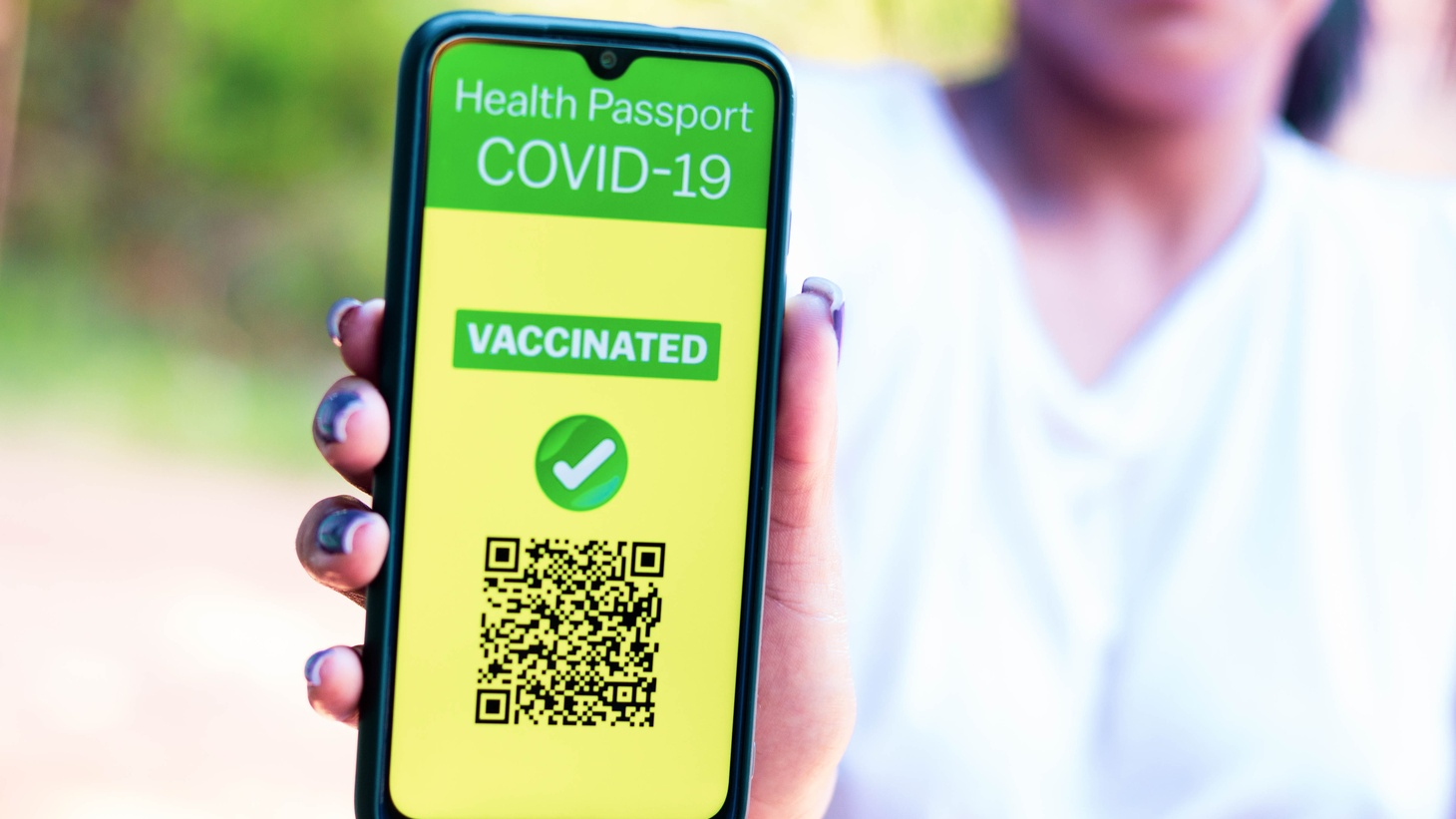 In this photo illustration, a woman shows digital proof that she's been vaccinated against COVID-19.