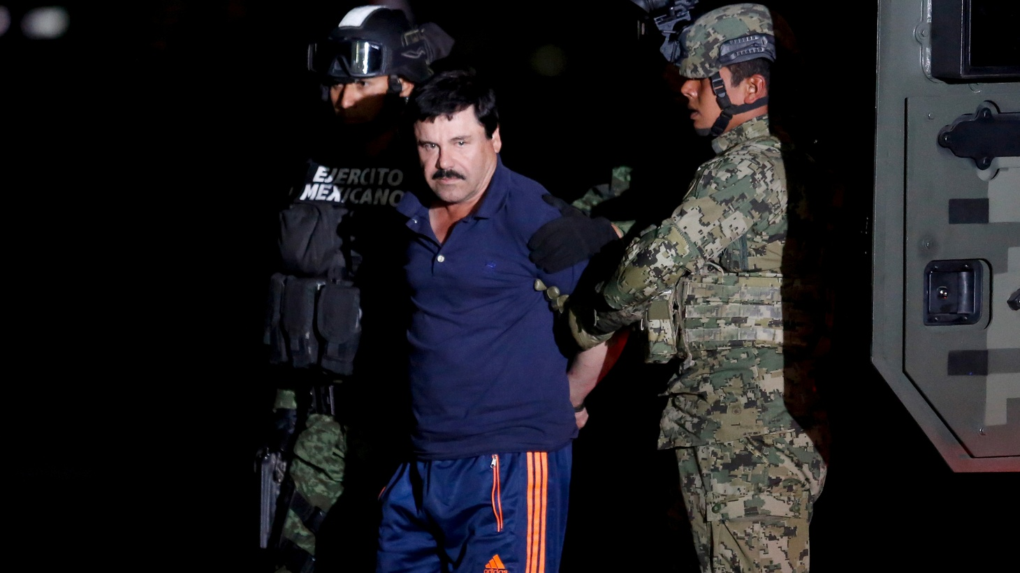"""Joaquin """"El Chapo"""" Guzman is escorted by soldiers during a presentation in Mexico City, January 8, 2016."""