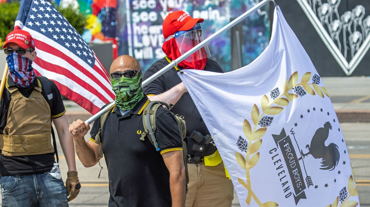 "Men wear ""Make America Great Again"" hats and carry large flags, including one that says ""Proud Boys Cleveland."" July 19, 2020."