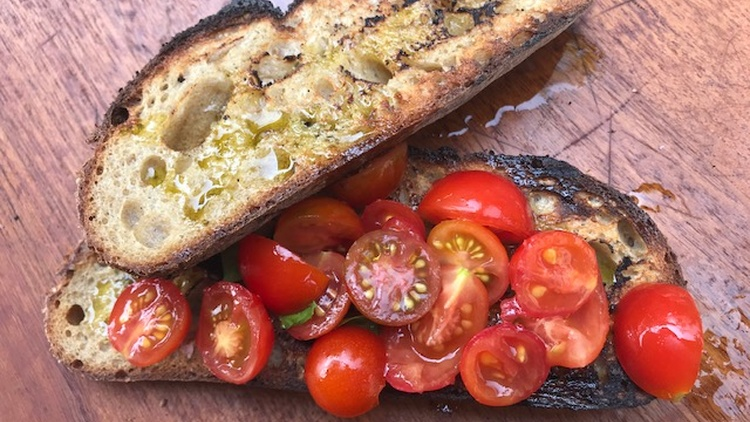 Bruschetta or fettunta (oiled slice) in Tuscany is toasted bread that's rubbed with a peeled garlic clove, sprinkled with salt, and doused with extra virgin olive oil.