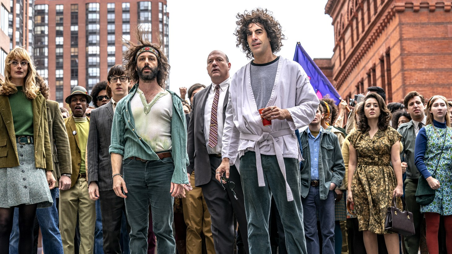 """(L-R) Caitlin Fitzgerald as Daphne O'connor, Alan Metoskie as Allen Ginsburg, Alex Sharp as Rennie Davis, Jeremy Strong as Jerry Rubin, John Carroll Lynch as David Dellinger, Sacha Baron Cohen as Abbey Hoffman, Noah Robbins as Lee Weiner in """"The Trial Of The Chicago 7"""""""