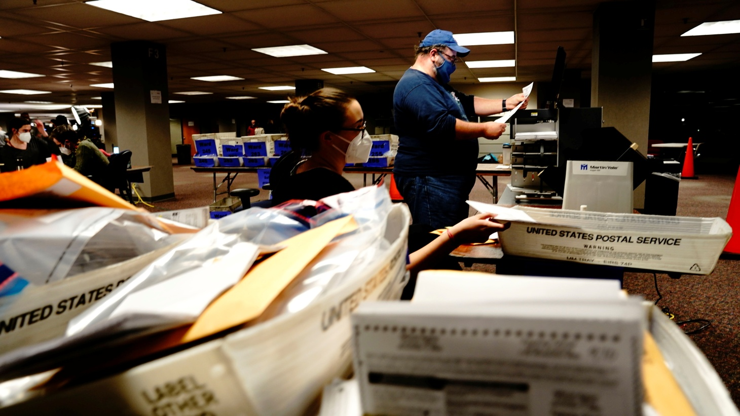 Poll workers Erin Keleske and Brett Rohlwing use a tabulator machine to process absentee ballots the night of Election Day at Milwaukee Central Count in Milwaukee, Wisconsin, U.S., November 3, 2020.