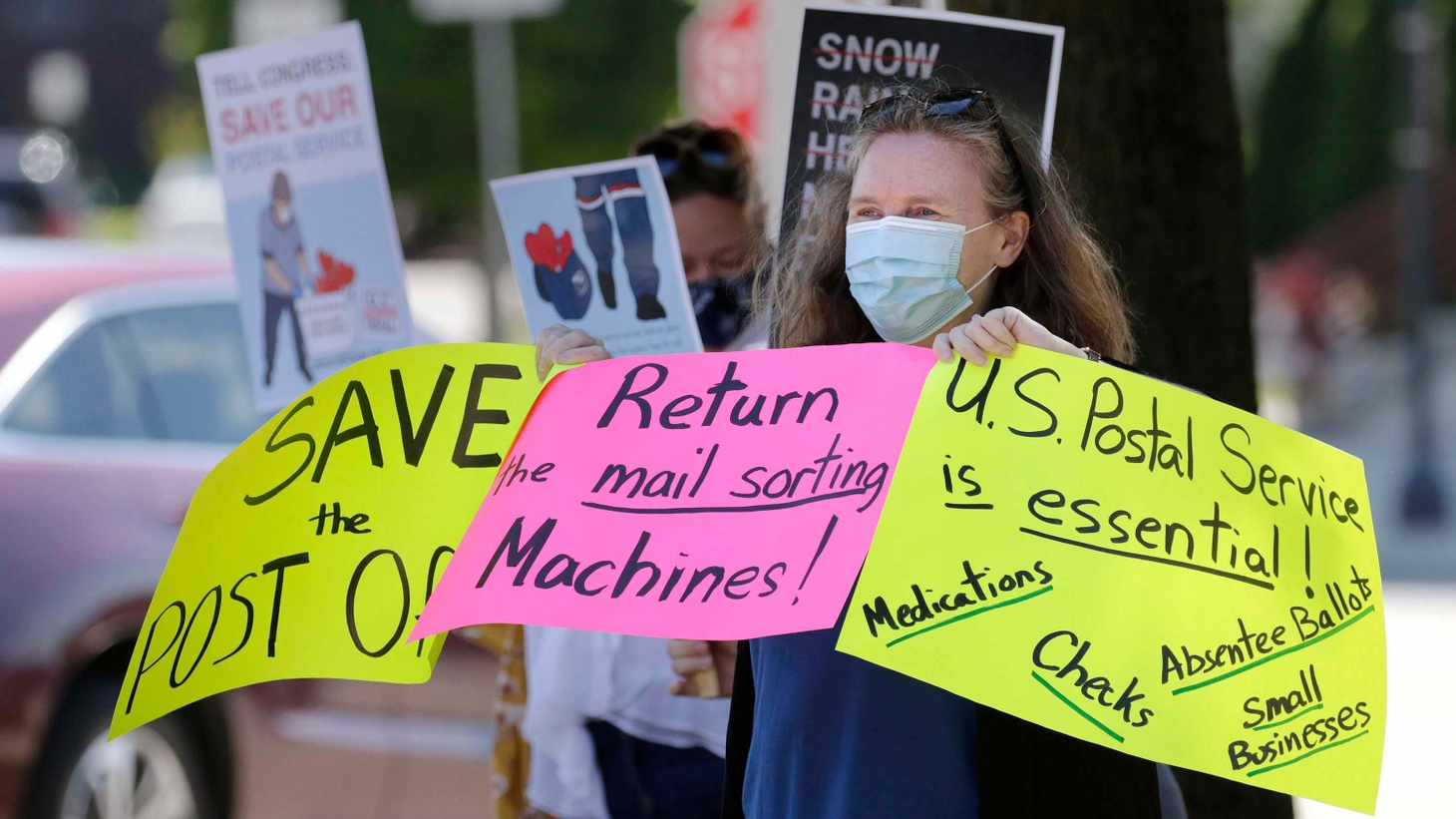 A woman holds signs of support for the U.S. Postal Service, Wednesday, August 19, 2020, in Sheboygan, Wis.