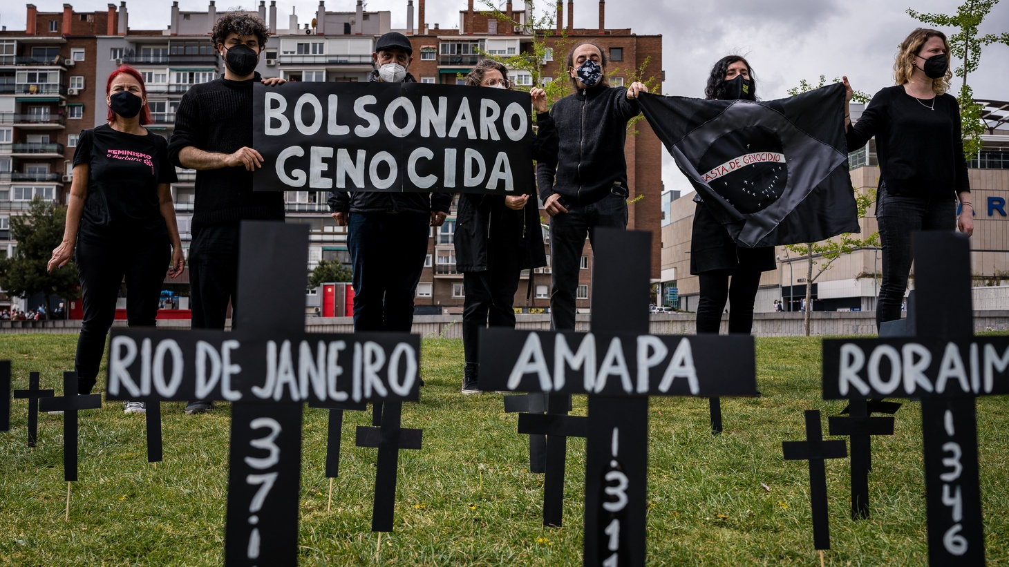 """Brazilian citizens are holding a """"Bolsonaro Genocidal"""" banner in Madrid Rio Park, where community members are remembering COVID-19 deaths in Brazil, and blaming President Jair Bolsonaro for the tragedy and poor management of the pandemic. April 1, 2021."""