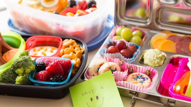 A quality lunch box with compartments can be filled with fresh fruit, veggies, cheese sticks, nuts, and a larger item like a tamale, pupusa, or quesadilla.
