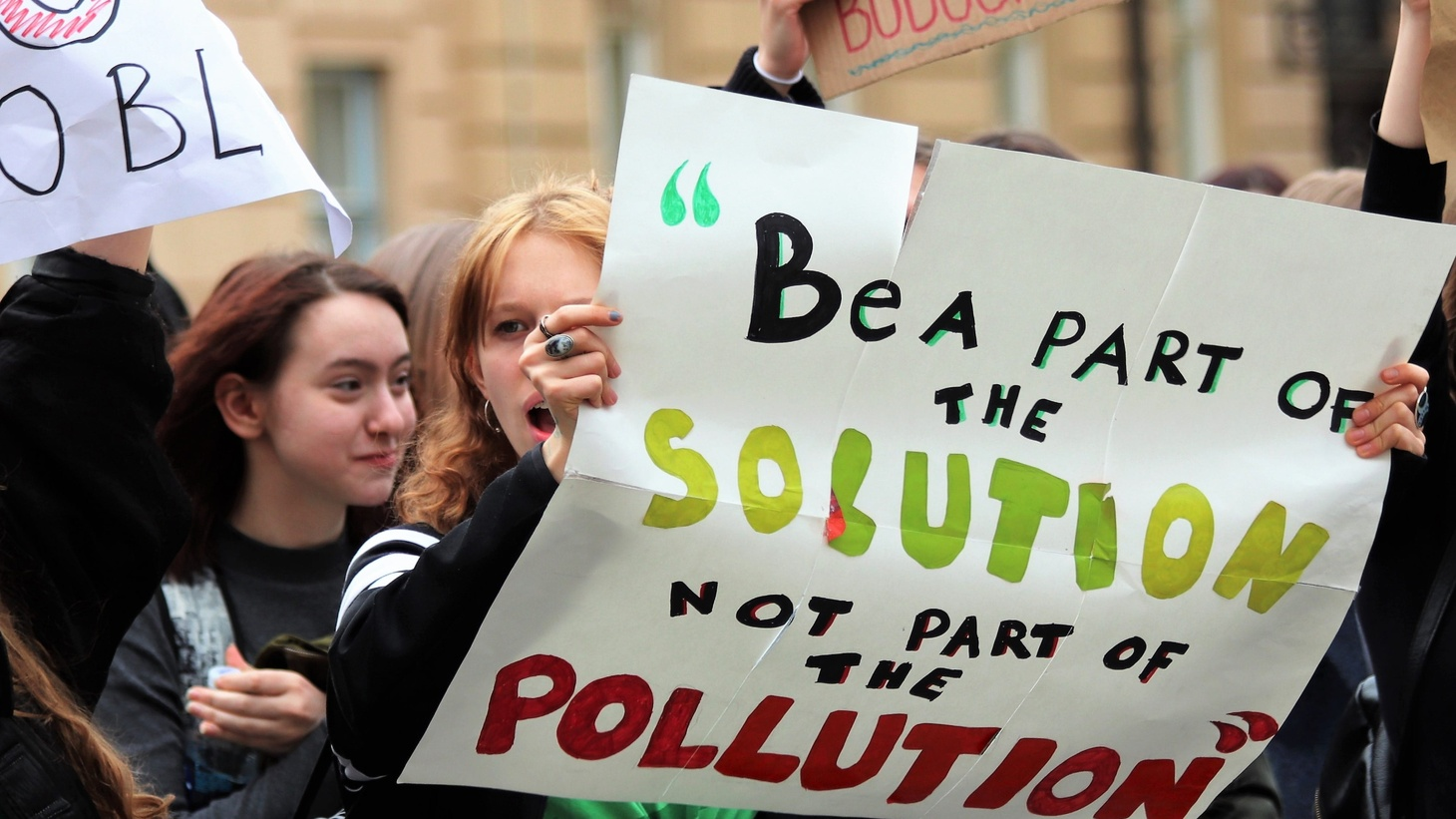 """A woman at a climate rally holds a sign saying, """"Be a part of the solution, not part of the pollution."""""""