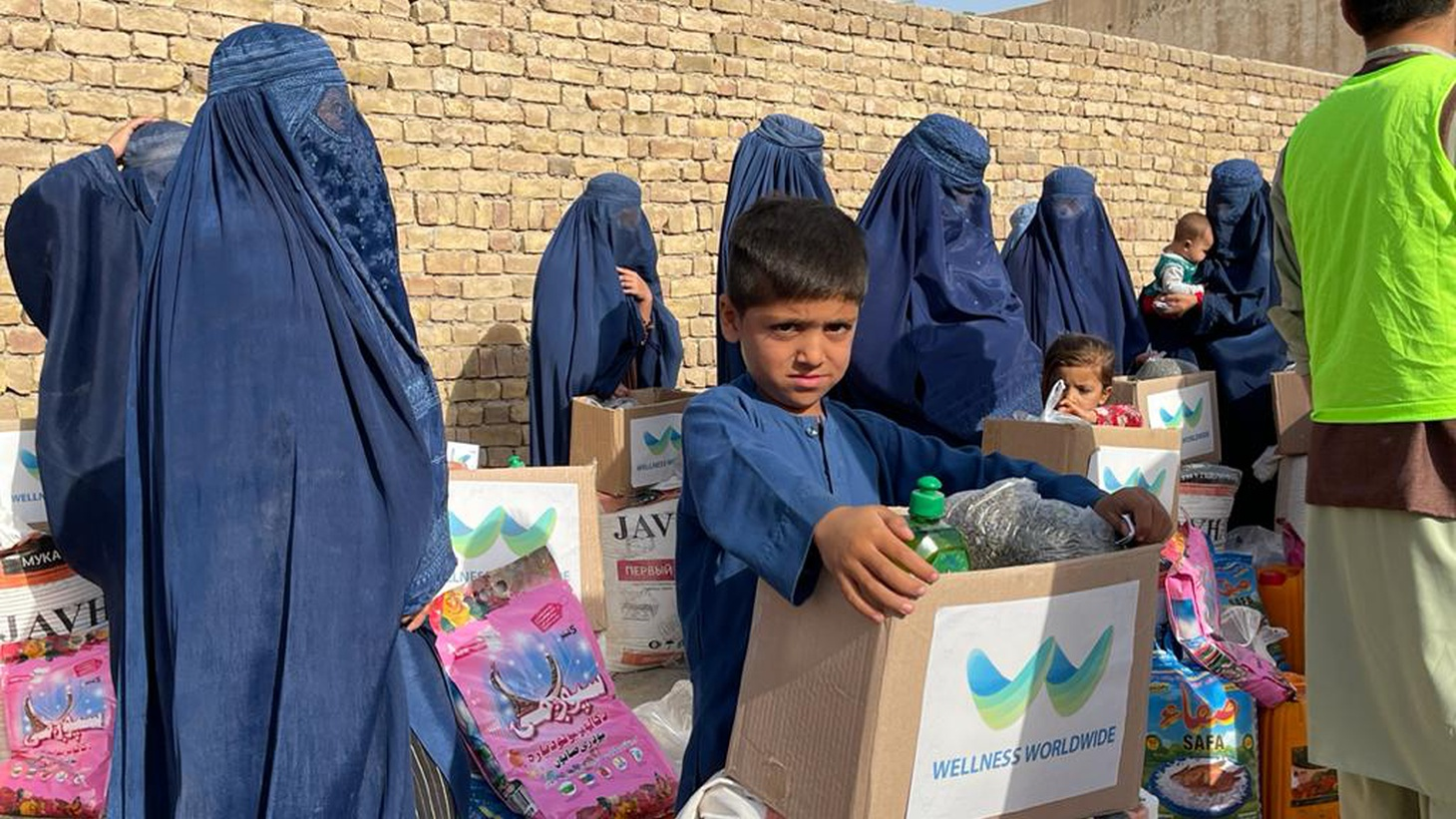 Women and children in the Afghan city of Kunduz line up at a food distribution site formed by the group Wellness Worldwide.