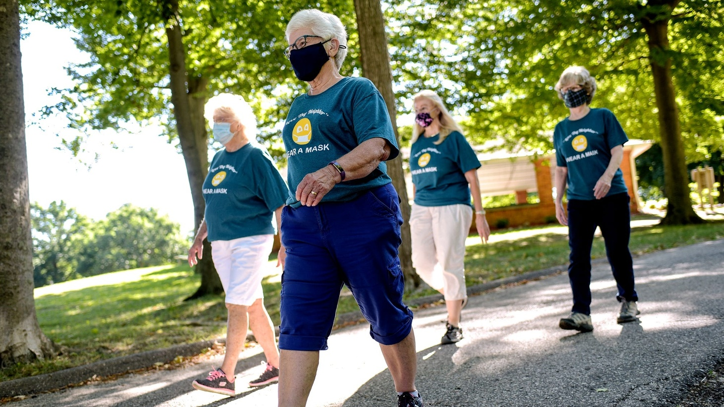 Sue Anderson, center, walks with a group of friends at St. Johns City Park on July 27, 2020. Anderson and the walking group are wearing shirts she is selling that suggest wearing a mask. The proceeds are being donated to a local needs center.